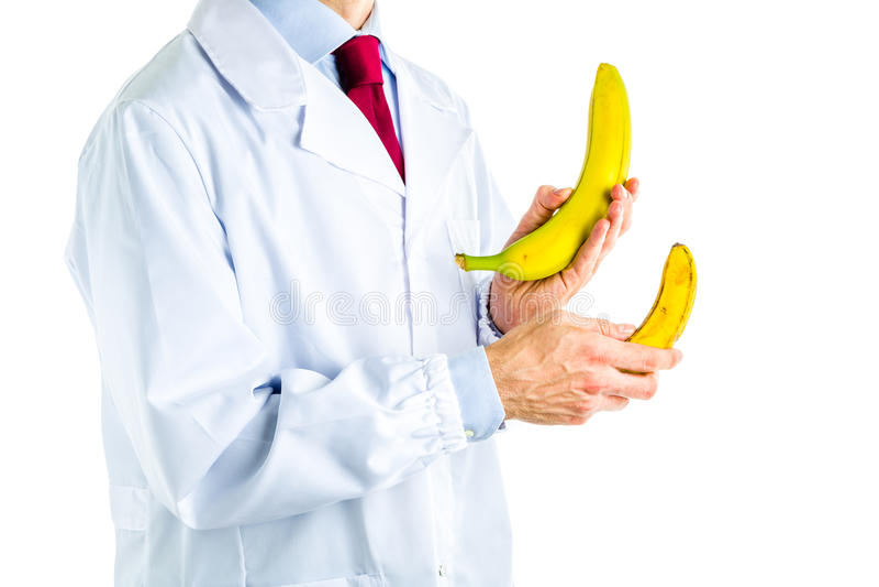 Γιατρός στο άσπρο παλτό που παρουσιάζει μεγάλες και μικρές μπανάνες στοκ φωτογραφίες