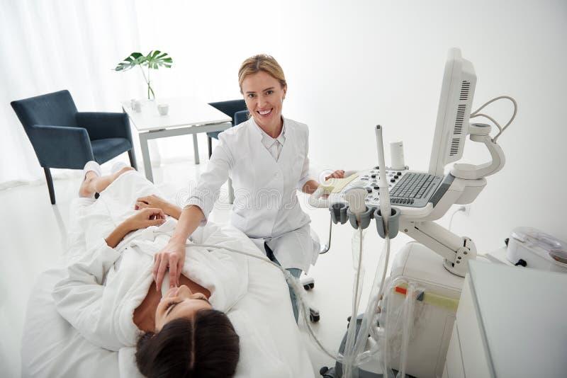 Γιατρός χρησιμοποιώντας τον ανιχνευτή υπερήχου και εξετάζοντας το γυναικείο θυροειδή αδένα στοκ φωτογραφία με δικαίωμα ελεύθερης χρήσης