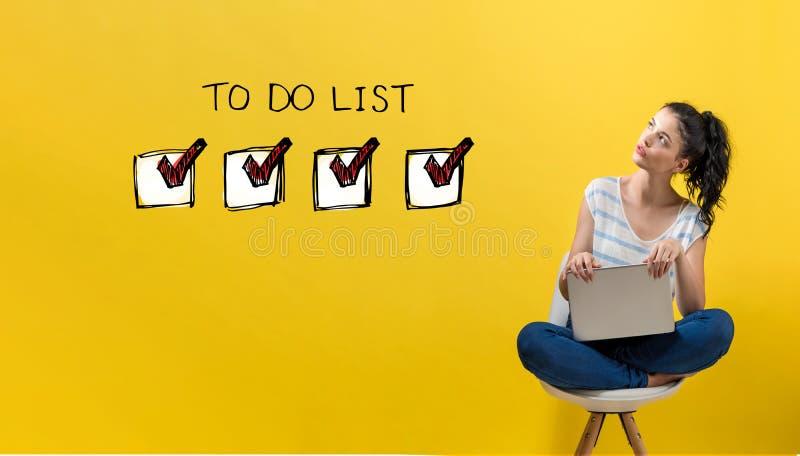 Για να κάνει τον κατάλογο με τη γυναίκα που χρησιμοποιεί ένα lap-top στοκ φωτογραφία