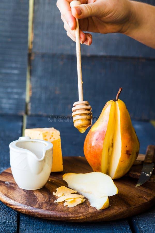 Για να χύσει στο μέλι τις φρέσκα φέτες και το τυρί αχλαδιών στοκ φωτογραφία