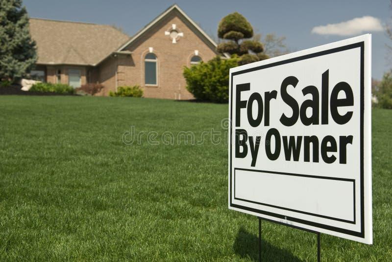 Για την πώληση του σημαδιού ιδιοκτητών μπροστά από το σπίτι στοκ εικόνα