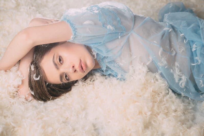 Για τον υγιή και ήρεμο ύπνο Όμορφο κορίτσι στις μεταξωτές πυτζάμες με το φτερό σε μακρυμάλλη Νέα γυναίκα στην ένδυση ύπνου χαριτω στοκ εικόνες