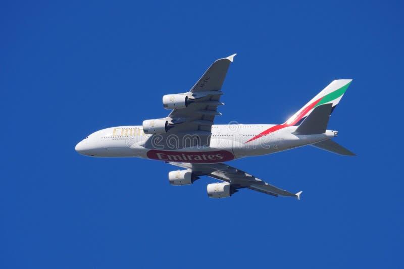Γιγάντιο αεροπλάνο Α380 των Εμιράτων εν πτήσει στον γαλάζιο ουρανό στοκ φωτογραφίες
