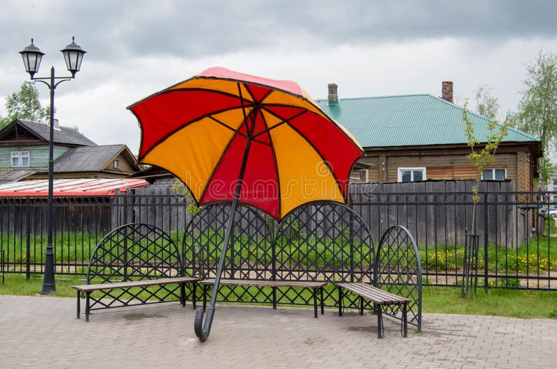 Γιγαντιαία ομπρέλα δίπλα στους πάγκους στοκ φωτογραφία