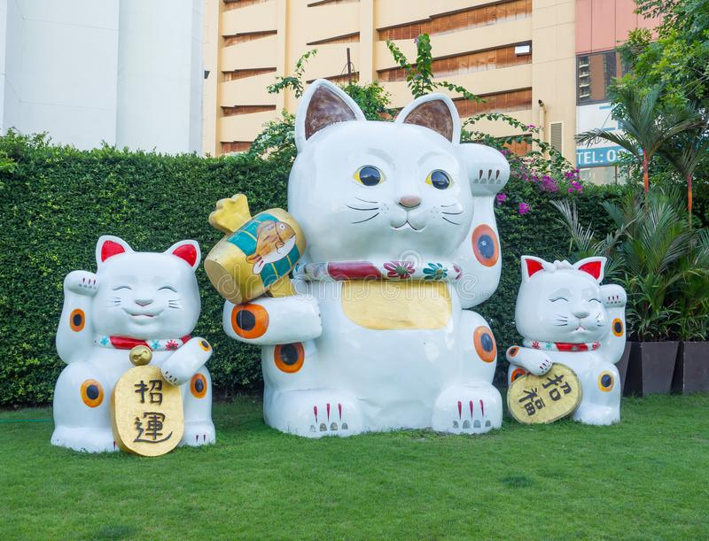 Γιγαντιαίο άσπρο ιαπωνικό τυχερό γλυπτό γατών σε μια ομάδα γάτας τριών οικογενειών στη λεωφόρο αγορών Ekamai πυλών στοκ εικόνα με δικαίωμα ελεύθερης χρήσης