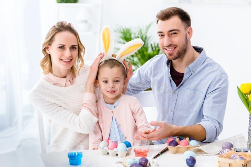 Γιορτάζοντας οικογένεια με το παιχνίδι κορών με τα αυτιά λαγουδάκι Πάσχας από τον πίνακα στοκ φωτογραφίες