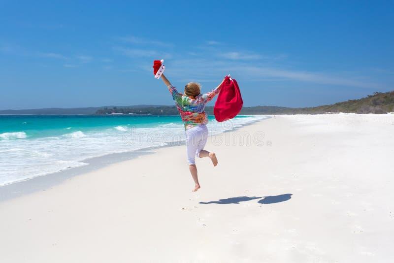 Γιορτάστε τα Χριστούγεννα στην Αυστραλία - θηλυκό που πηδά για τη χαρά στο bea στοκ φωτογραφίες