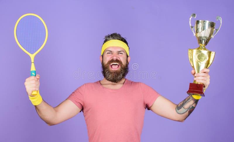 Γιορτάστε τη νίκη Αθλητική ρακέτα αντισφαίρισης λαβής ατόμων και χρυσό goblet Κερδίστε το παιχνίδι αντισφαίρισης Ο τενίστας κερδί στοκ εικόνες