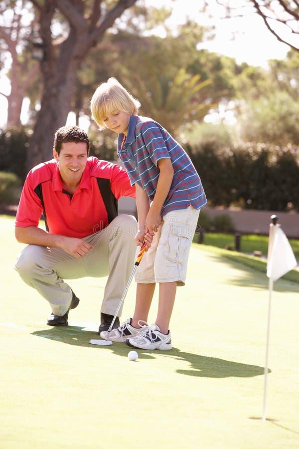 Γιος διδασκαλίας πατέρων για να παίξει το γκολφ στοκ φωτογραφία