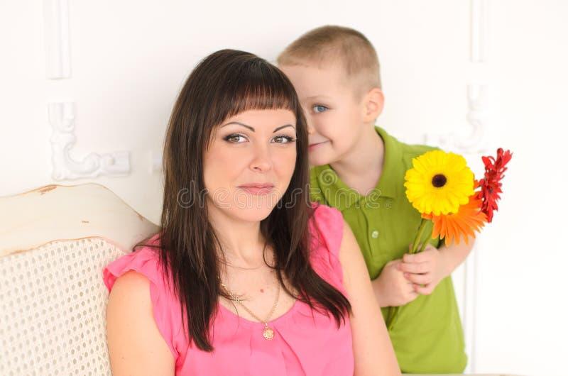 γιος με τα λουλούδια με το mom στοκ εικόνα με δικαίωμα ελεύθερης χρήσης