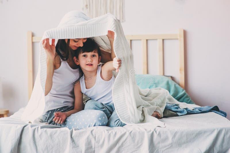 Γιος μητέρων και παιδιών που απολαμβάνει το πρωί Σαββατοκύριακου στο κρεβάτι, περιστασιακός τρόπος ζωής στοκ εικόνες με δικαίωμα ελεύθερης χρήσης