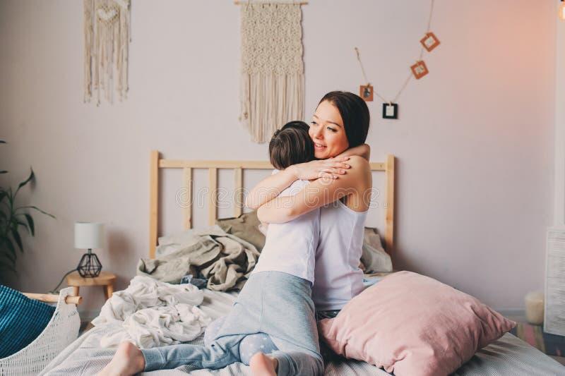 Γιος μητέρων και παιδιών που απολαμβάνει το πρωί Σαββατοκύριακου στο κρεβάτι, περιστασιακός τρόπος ζωής στοκ εικόνα με δικαίωμα ελεύθερης χρήσης
