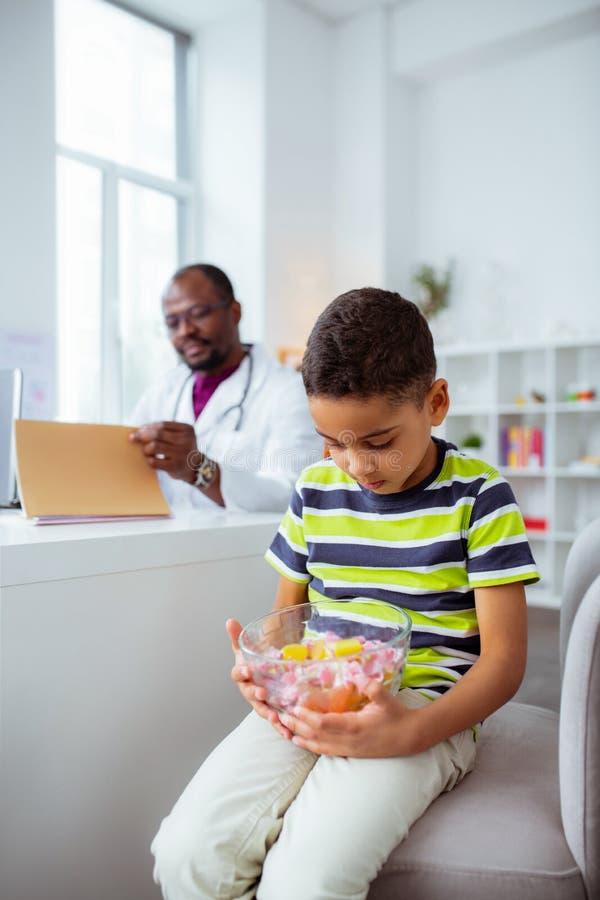 Γιος που εξετάζει τις καραμέλες που επισκέπτονται την εργασία πατέρων ως γιατρό στο νοσοκομείο στοκ φωτογραφία