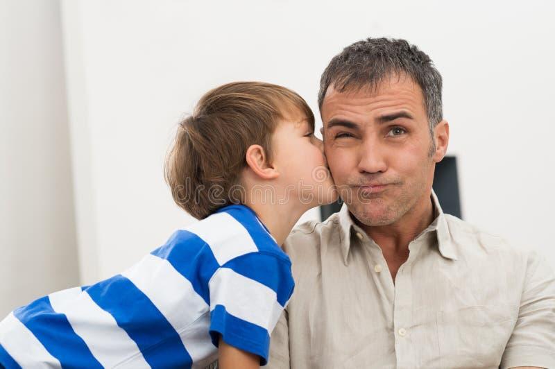 Γιος που φιλά τον πατέρα του στοκ φωτογραφία