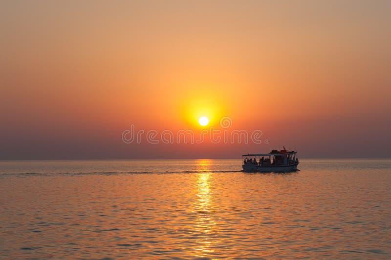 Γιοτ, βάρκα, βάρκα στον ορίζοντα και η σκιαγραφία ενός όμορφου ηλιοβασιλέματος, καυτό ηλιοβασίλεμα κρουαζιερόπλοιο στοκ φωτογραφίες
