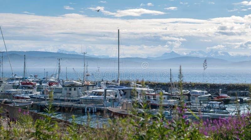 Γιοτ και βάρκες σε μια πρόσδεση σε ένα υπόβαθρο του νεφελωδών ουρανού και των βουνών στοκ φωτογραφίες με δικαίωμα ελεύθερης χρήσης