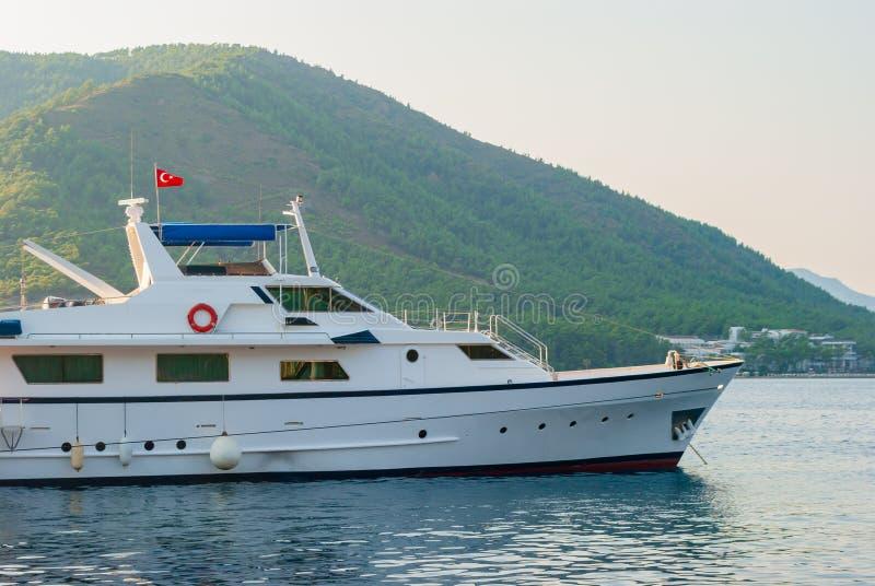 Γιοτ που πλέει στη θάλασσα με τη σημαία της Τουρκίας κοντά στην πόλη και τα βουνά στοκ εικόνες