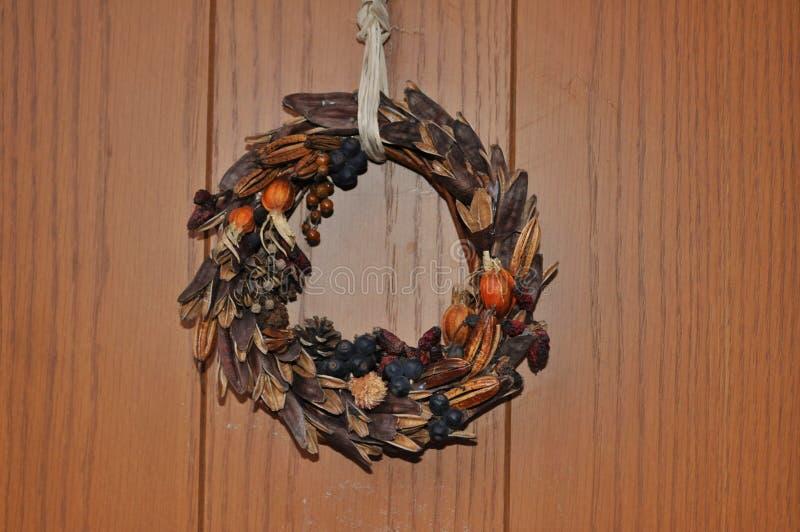 Γιρλάντα που κρεμιέται μπροστά από μια ξύλινη πόρτα στοκ εικόνες