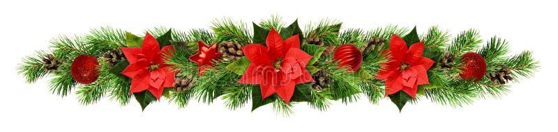 Γιρλάντα Χριστουγέννων με τα κόκκινα λουλούδια pionsettia, τους κλαδίσκους πεύκων και το de στοκ φωτογραφία