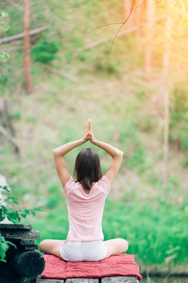 Γιόγκα άσκησης γυναικών στα ξύλα, στη φύση, που κάθεται πίσω Υγεία, ασκήσεις πρωινού στοκ φωτογραφία