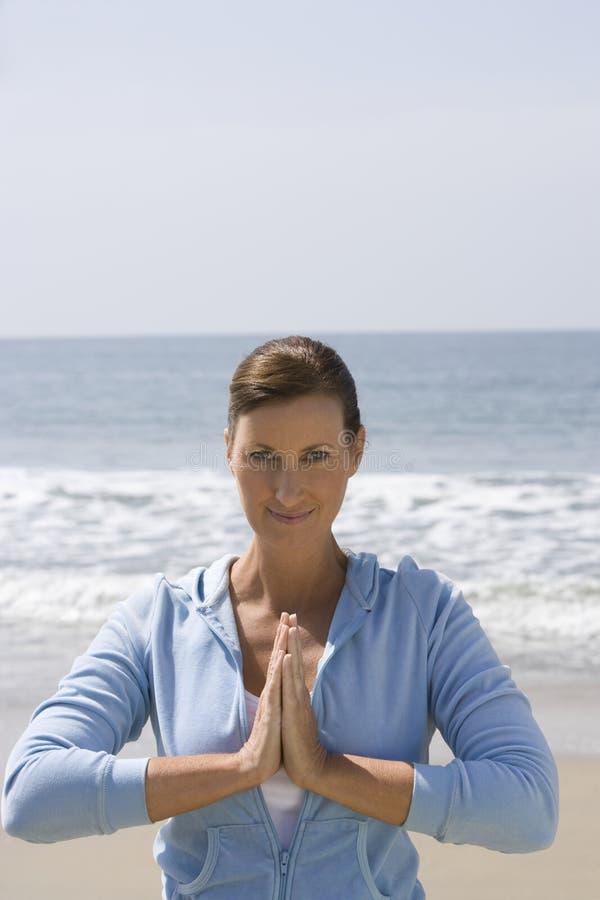 Γιόγκα άσκησης γυναικών στην παραλία στοκ φωτογραφία