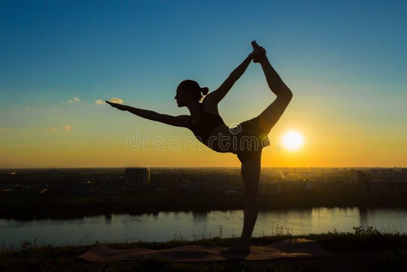 Γιόγκα άσκησης γυναικών στο πάρκο στο ηλιοβασίλεμα - ο Λόρδος του χορού θέτει στοκ εικόνα