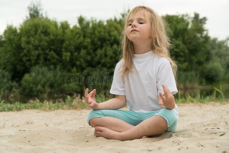 Γιόγκα άσκησης κοριτσιών στην παραλία o στοκ εικόνες