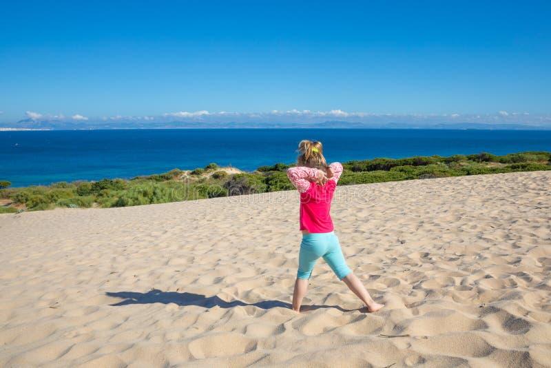 Γιόγκα άσκησης μικρών κοριτσιών στον αμμόλοφο με την Αφρική στον ορίζοντα στοκ φωτογραφία