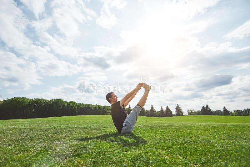 Γιόγκα άσκησης Φίλαθλο τέντωμα νεαρών άνδρων υπαίθρια σε έναν πράσινο χορτοτάπητα στον ανοικτό τομέα σε ένα ηλιόλουστο πρωί Περισ στοκ εικόνες