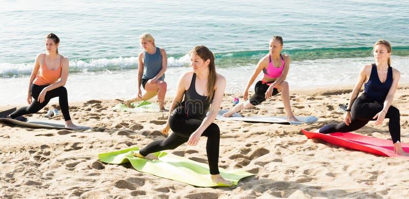 Γιόγκα στην παραλία θάλασσας, ομάδα κατάρτισης γυναικών στοκ φωτογραφία με δικαίωμα ελεύθερης χρήσης