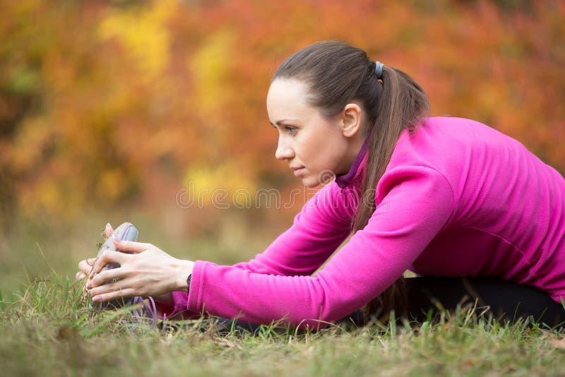 Γιόγκα φθινοπώρου: Η καθισμένη μπροστινή γιόγκα κάμψεων θέτει στοκ εικόνες
