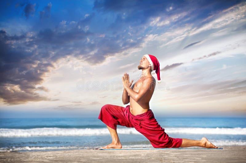 Γιόγκα Χριστουγέννων στην παραλία στοκ φωτογραφία