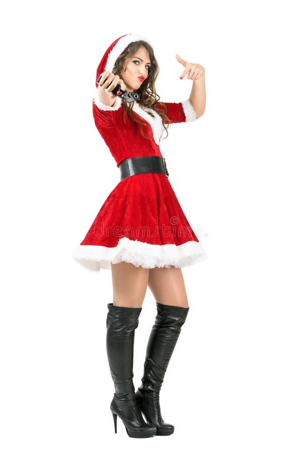 Γκάγκστερ θηλυκός Άγιος Βασίλης που στοχεύει το πυροβόλο όπλο στη κάμερα στοκ φωτογραφίες με δικαίωμα ελεύθερης χρήσης