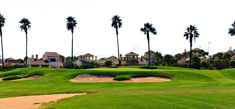 Γκολφ πράσινο στην Ισπανία με τα σπίτια και τα threes φοινικών γύρω στοκ φωτογραφίες