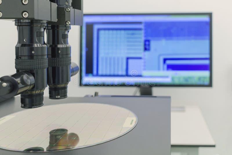 Γκοφρέτα πυριτίου στη διαδικασία μηχανών που εξετάζει στο μικροσκόπιο στοκ φωτογραφία