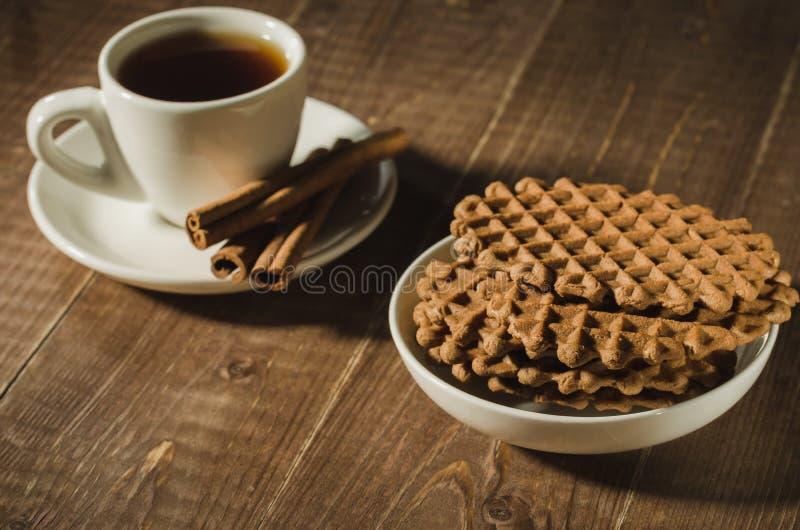 γκοφρέτες και φλιτζάνι του καφέ σοκολάτας με τα ραβδιά κανέλας/τις γκοφρέτες σοκολάτας και φλιτζάνι του καφέ με τα ραβδιά κανέλας στοκ φωτογραφίες