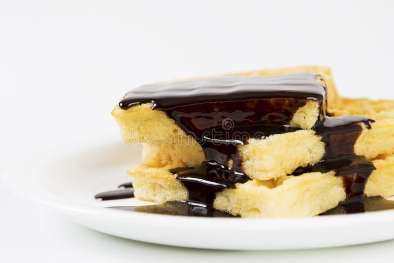 Γκοφρέτες που χύνονται από τη λειωμένη σκοτεινή σοκολάτα στοκ εικόνες με δικαίωμα ελεύθερης χρήσης