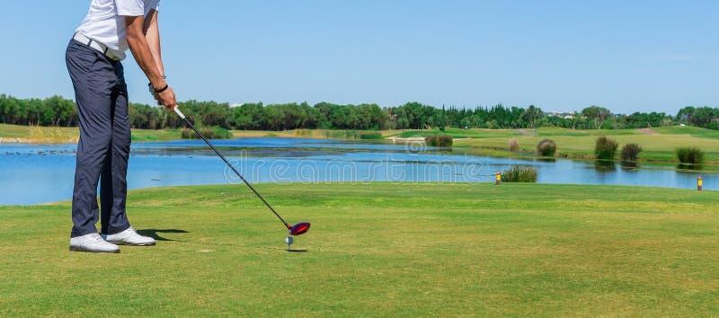 Γκολφ παιχνιδιού ατόμων Με το ραβδί στον πράσινο τομέα στοκ εικόνα