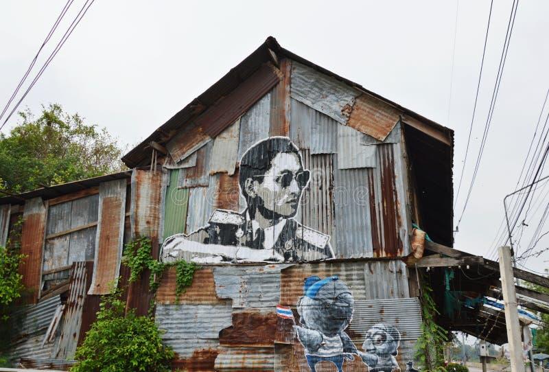 Γκράφιτι για το μνημείο στο βασιλιά Bhumibol Adulyadej Αυτού Εξοχότη στον παλαιό τοίχο σπιτιών στοκ εικόνες