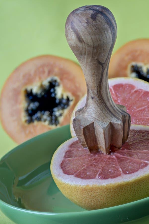 Γκρέιπφρουτ και ξύλινο squeezer λεμονιών στοκ εικόνα με δικαίωμα ελεύθερης χρήσης
