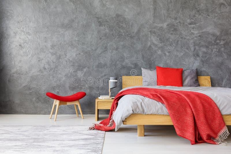 Γκρίζα κρεβατοκάμαρα με τις κόκκινες εμφάσεις στοκ εικόνα