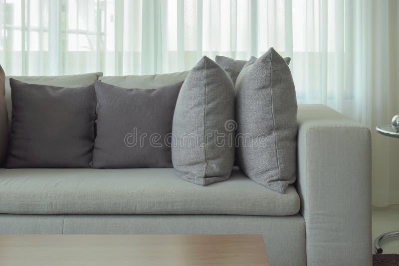 Γκρίζα μαξιλάρια στον μπεζ καναπέ χρώματος με την παρέκκλιση στο υπόβαθρο στοκ φωτογραφία με δικαίωμα ελεύθερης χρήσης