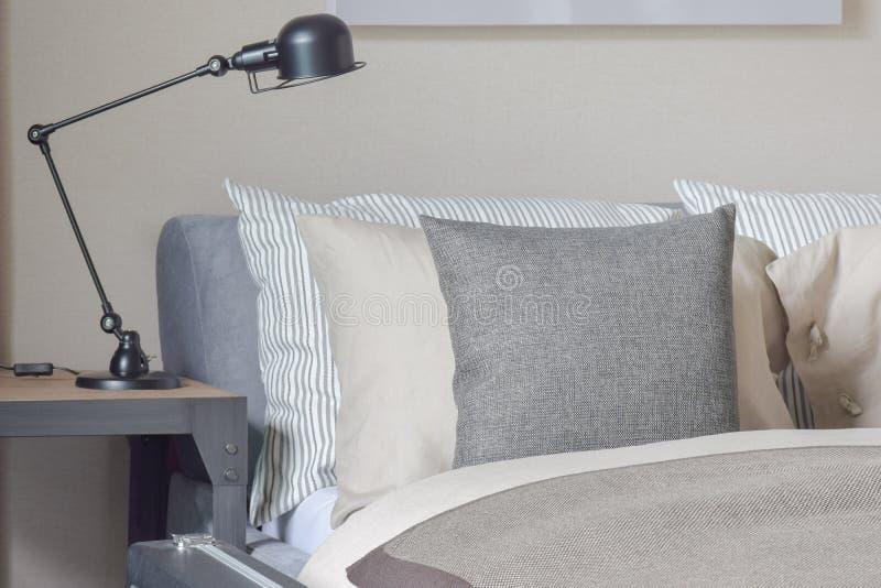 Γκρίζα, μπεζ και γδυμένα μαξιλάρια που θέτουν στο κρεβάτι με το μαύρο λαμπτήρα ανάγνωσης στοκ εικόνες