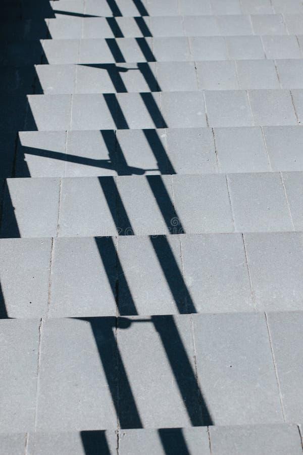 Γκρίζα σκάλα που πηγαίνει κάτω, με τη σκιά από το κιγκλίδωμα στοκ φωτογραφία με δικαίωμα ελεύθερης χρήσης