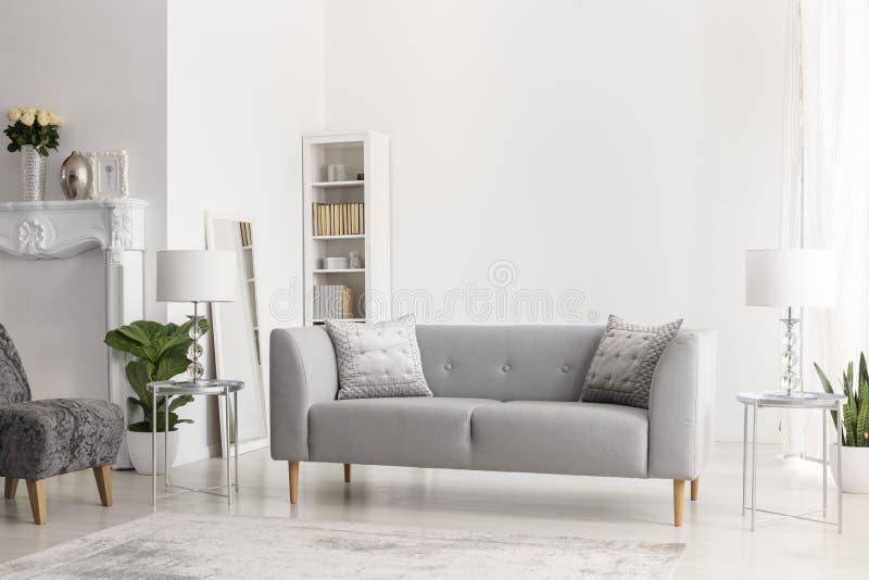 Γκρίζοι καναπές και λαμπτήρες στους ασημένιους πίνακες στο άσπρο εσωτερικό διαμερισμάτων με τα λουλούδια και την πολυθρόνα Πραγμα στοκ εικόνα με δικαίωμα ελεύθερης χρήσης