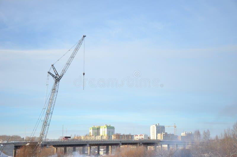 Γκρίζος γερανός πύργων που υψώνεται πέρα από τη γέφυρα στο υπόβαθρο των πολυκατοικιών και του μπλε ουρανού στοκ φωτογραφία με δικαίωμα ελεύθερης χρήσης