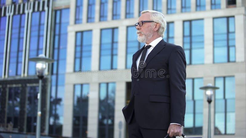 Γκρίζος-μαλλιαρός διευθυντής επιχείρησης που στέκεται υπαίθρια, βέβαια αναμονή επιχειρηματιών στοκ εικόνες
