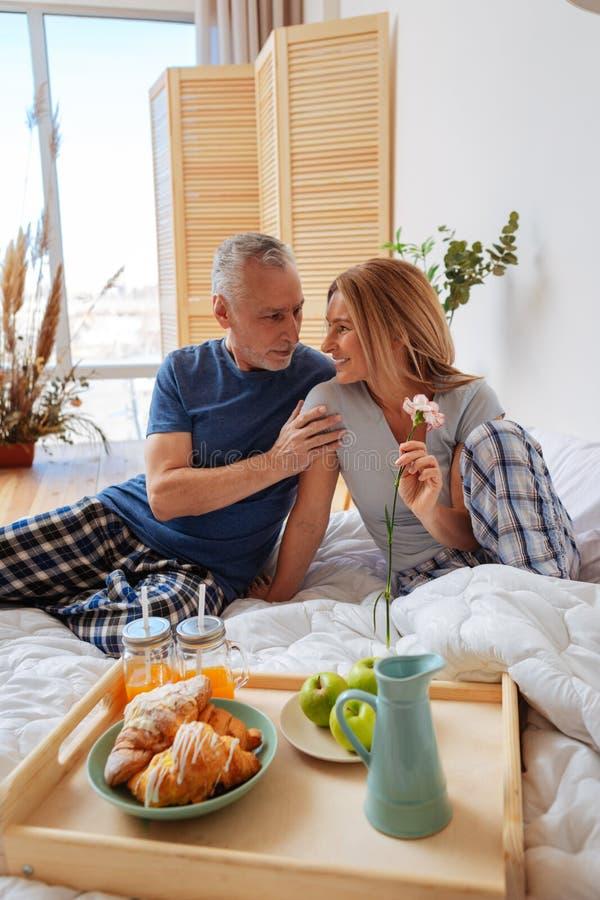 Γκρίζος-μαλλιαρός σύζυγος που εξετάζει την ακτινοβολώντας σύζυγό του ενώ έχοντας το πρόγευμα στοκ φωτογραφίες με δικαίωμα ελεύθερης χρήσης