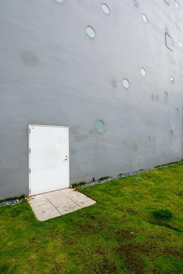 Γκρίζος τοίχος με την άσπρη πόρτα στοκ εικόνα