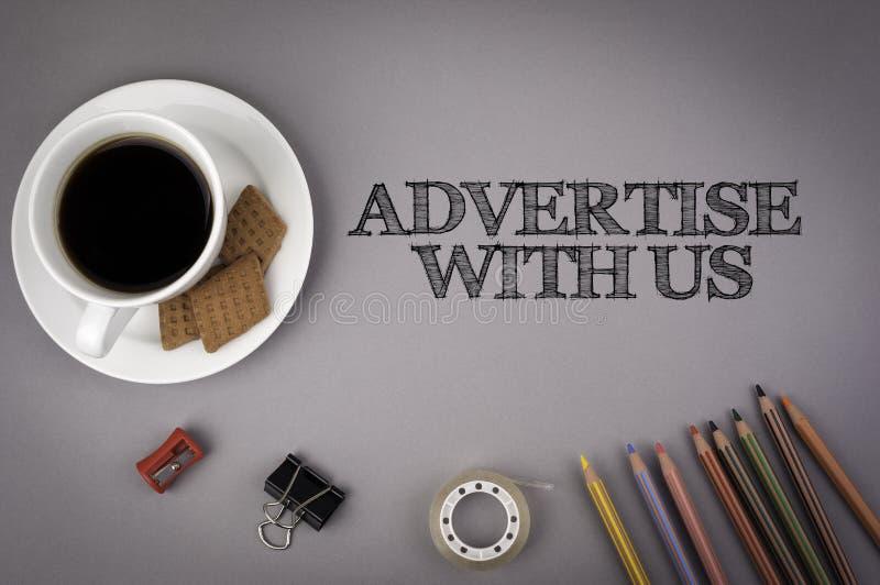 Γκρίζο γραφείο γραφείων με την επιγραφή - διαφημίστε με μας στοκ φωτογραφία